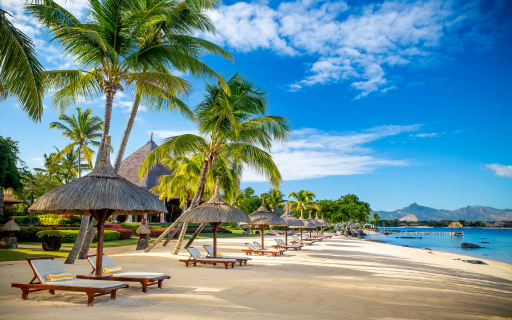 morning view of the beach at The Oberoi Mauritius with palm trees and blue sky